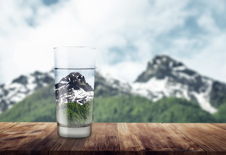 glass of water on wooden table. blurred snow mountains tops and green forests at the background, as a symbol of freshness and purity
