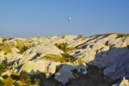 peculiar: Hot air balloons flying over the peculiar geological formations of Cappadocia Stock Photo