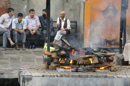 KATHMANDU,NP CIRCA AUGUST 2012 - Burning corpse in Pashupatinath Temple circa August 2012 in Kathmandu. The Pashupatinath Temple, located at the bank of the river Bagmati, is considered the most sacred place in Nepal.
