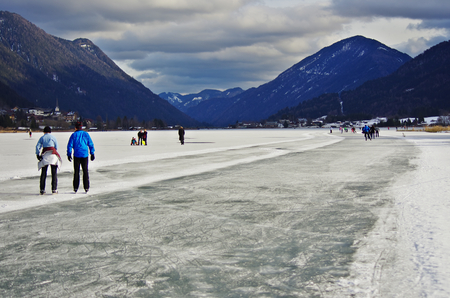 iceskating: WEISSENSEE,AT - DECEMBER,24 2012 -  People skate on the iced surface of the lake. Editorial