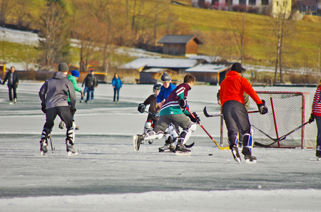 sportsmanship: WEISSENSEE,AT - DECEMBER,24 2012 -  Young boys play hockey on the iced surface of the lake Editorial