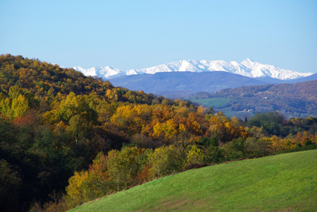 Mount Cusna covered with snow above the hills in autumn colours.