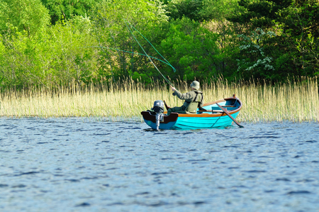 Fly fishing from a boat on Irish lake Stock Photo