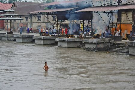 KATHMANDU,NP - CIRCA AUGUST, 2012 - Boy baths in the river Bagmati at the Pashupatinath temple, while on the bank people are cremating corpses.
