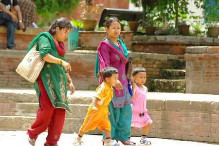 struck: KATHMANDU,NP - CIRCA AUGUST, 2012 - Two women with children walk in Durbar square.   Nepal will be struck by a big earthquake in 2015.