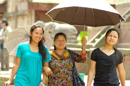 KATHMANDU,NP - CIRCA AUGUST, 2012 -  Three women walk in Durbar square and protect form the sun with an umbrella. Nepal will be struck by a big earthquake in 2015.