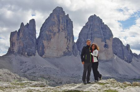 Young attractive couple of hikers in front of Tre Cime di Lavaredo, Dolomites