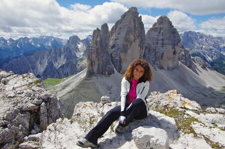 Young attractive female hiker on top of Paterno in front of Tre Cime di Lavaredo Stock Photo