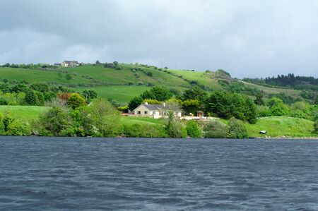 House on a lake in Ireland: dramatic landscape Stock Photo