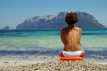 edge: Attractive young woman sitting on the beach in front of Tavolara Island, Sardinia Italy..