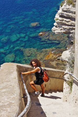 Young female tourist descending the stairs carved in the cliffs of Bonifacio, below the Medieval citadel.