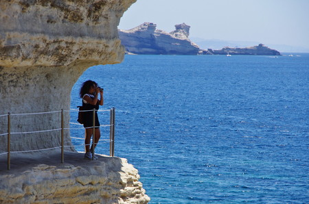 Female tourist walking on a passage carved into the cliffs near the sea level, below the medieval citadel of Bonifacio. Stock Photo