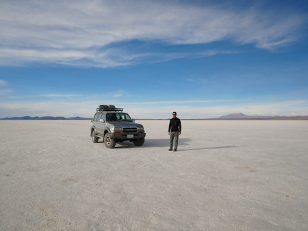 Uyuni, BO - CIRCA October 2018 - Young male tourist at the incredible salt flat of Salar de Uyuni, on the andean altiplano of Bolivia, South America, seen from the Isla Incahuasi, an island emerging f