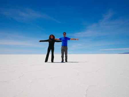 Young couple of tourist at the incredible salt flat of Salar de Uyuni, on the andean altiplano of Bolivia, South America, seen from the Isla Incahuasi, an island emerging from the salt 版權商用圖片