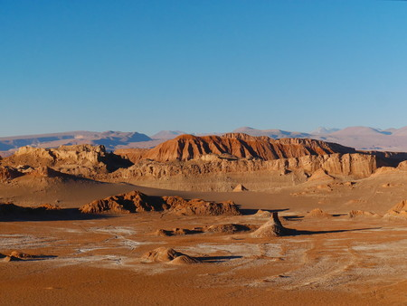 The incredible red rocks of the Moon Valley (Valle de la luna) near San Pedro De Atacama at sunset, with andean volcano Licancabur in the distance. Atacama desert is known as the driest place on earth.