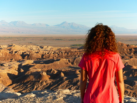 Young adult tourist at the incredible red rocks of the Moon Valley (Valle de la luna) near San Pedro De Atacama at sunset, with andean volcano Licancabur in the distance. Atacama desert is known as th 写真素材