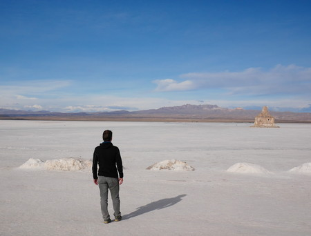Young male tourist at the incredible salt flat of Salar de Uyuni, on the andean altiplano of Bolivia, South America, seen from the Isla Incahuasi, an island emerging from the salt