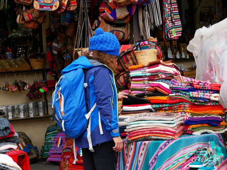 Colorful textiles in the market of Purmamarca, Argentina. Alpaca wool. Young female tourist.