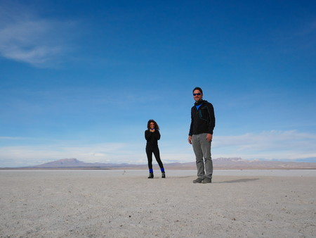 Young couple of tourist at the incredible salt flat of Salar de Uyuni, on the andean altiplano of Bolivia, South America, seen from the Isla Incahuasi, an island emerging from the salt 報道画像