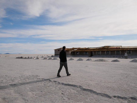 Young male tourist at the incredible salt flat of Salar de Uyuni, on the andean altiplano of Bolivia, South America, seen from the Isla Incahuasi, an island emerging from the salt 写真素材 - 117654548