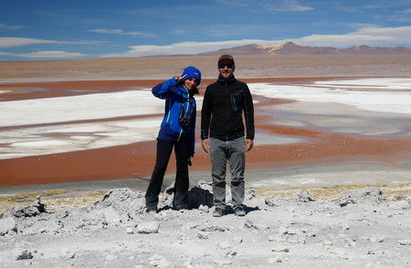 Young adult couple tourist at Laguna Colorada, Coloured Lagoon, takes its colour from algae and its populated by thousands of flamingos. Andean altiplano of Bolivia, South America 報道画像