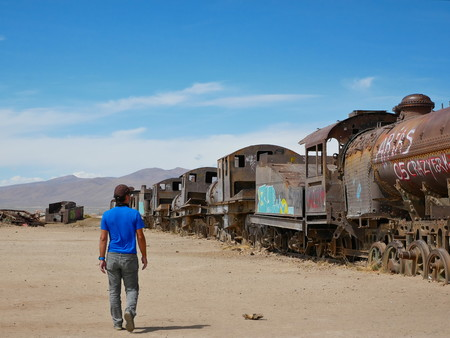 Train cemetary near Uyuni, Bolovia. Andean altiplano of Bolivia, South America. Young man standing. 報道画像
