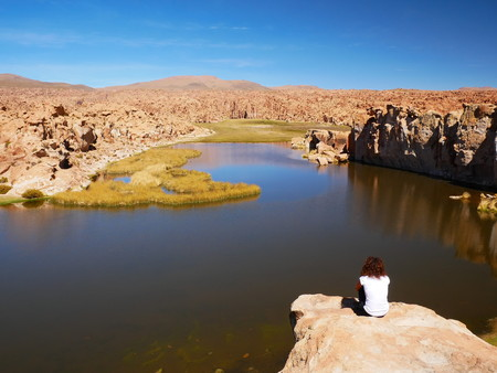 Young tourist at Laguna Escondida and rock formations. Andean altiplano of Bolivia, South America 写真素材