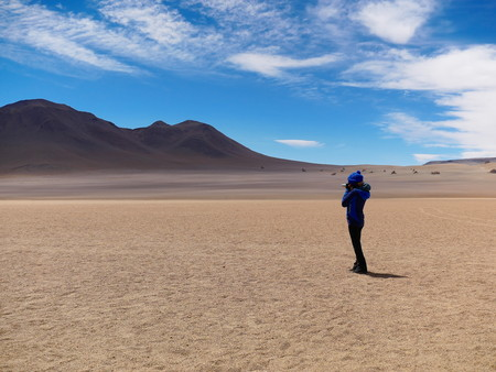 Desert of Bolivia looks like paintings by Salvador Dalì. Andean altiplano of Bolivia, South America. Young tourist standing