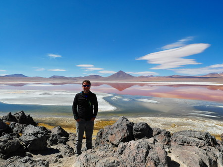 Young male tourist at Laguna Colorada, Coloured Lagoon, takes its colour from algae and its populated by thousands of flamingos. Andean altiplano of Bolivia, South America