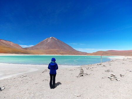 Green lagoon an Licancabur volcano on the Andean altiplano of Bolivia, South America. Young female tourist standing.
