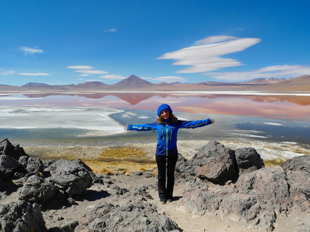 Young female tourist at Laguna Colorada, Coloured Lagoon, takes its colour from algae and its populated by thousands of flamingos. Andean altiplano of Bolivia, South America