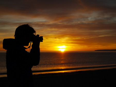 A scenic red sunrise on the coast of Puerto Madryn, Patagonia Argentina. Young man photographing silhouette 写真素材