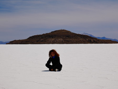 Young female tourist at the incredible salt flat of Salar de Uyuni, on the andean altiplano of Bolivia, South America, seen from the Isla Incahuasi, an island emerging from the salt