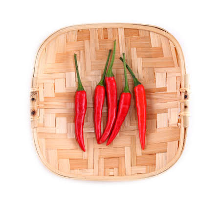 Red pepper on bamboo plate, on a white background photo