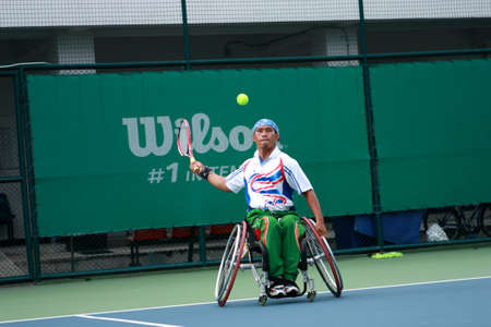 A wheelchair tennis player during a tennis championship match, taking a shot  版權商用圖片