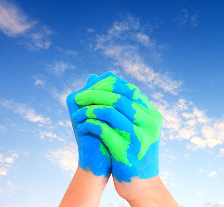 Map of world painted on hands in the blue sky   photo