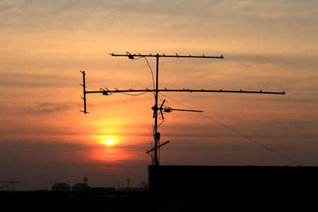 logarithmic: Silhouette front view of a roof pole mounted wide band logarithmic terrestrial TV home reception aerial, with addictional mounted UHF plugin antenna to improve UHF signals reception Sunset in the background   Stock Photo