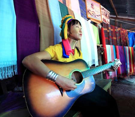 pinkie: MAE HONG SON, THAILAND -NOVEMBER 23: Karen long neck hill tribe women playing guitar show for tourist at village,Ban Huay sue toa where tourist visiting, November 23th 2013 in Mae hong son, Thailand