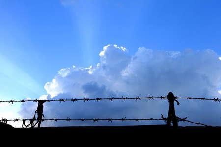prisoner of war: Barbed wire wall on blue sky