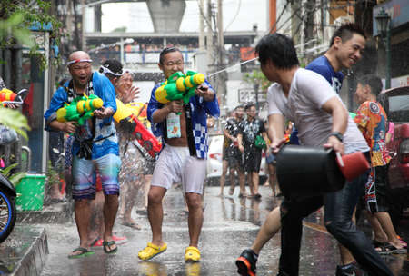 silom: BANGKOK - APRIL 13  Stream of water over the crowd of people during celebrating the traditional Songkran New Year Festival, April 13, 2012, Silom road, Bangkok, Thailand