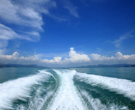Fluffy clouds over the ocean and waves of the boat Stock Photo