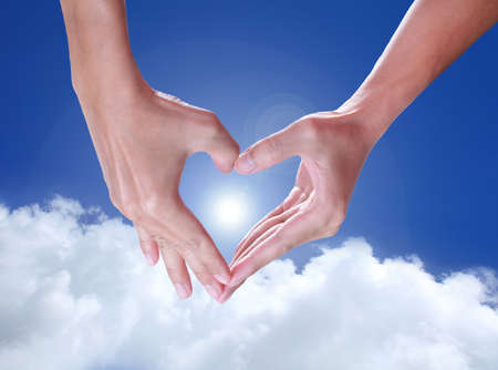 hands holding signs love on blue sky photo