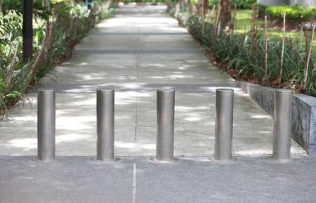 Steel barrier on the sidewalk in the park