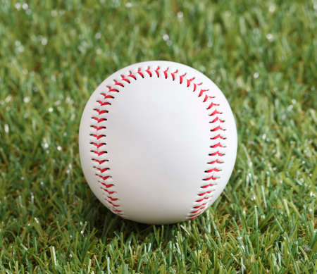 A white used baseball on the fresh green grass photo