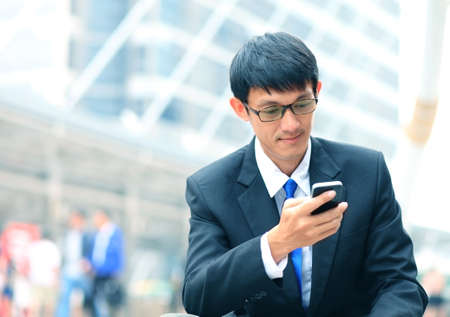 office phone: Man on smart phone - young business man. Casual urban professional businessman using smartphone smiling happy outside office building. Handsome man wearing suit outdoors.