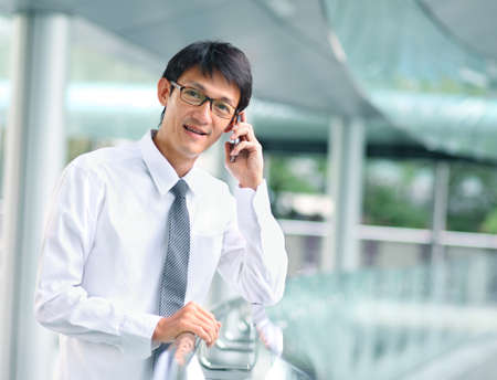 Portrait of young businessman talking with smartphone photo