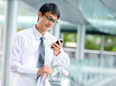 Portrait of young businessman talking with smartphone. photo