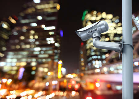 CCTV camera with blurring the night city in background. photo