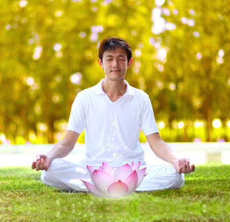 young man meditating in autumn park. photo