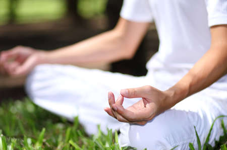 Young man during relaxation and meditation in park meditation session. Frame shows half of body.